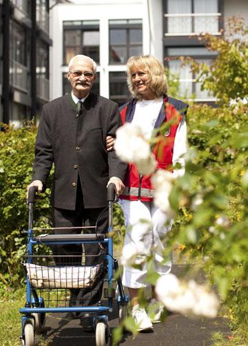 Foto: Pflegekraft beim Spaziergang mit einem Senioren